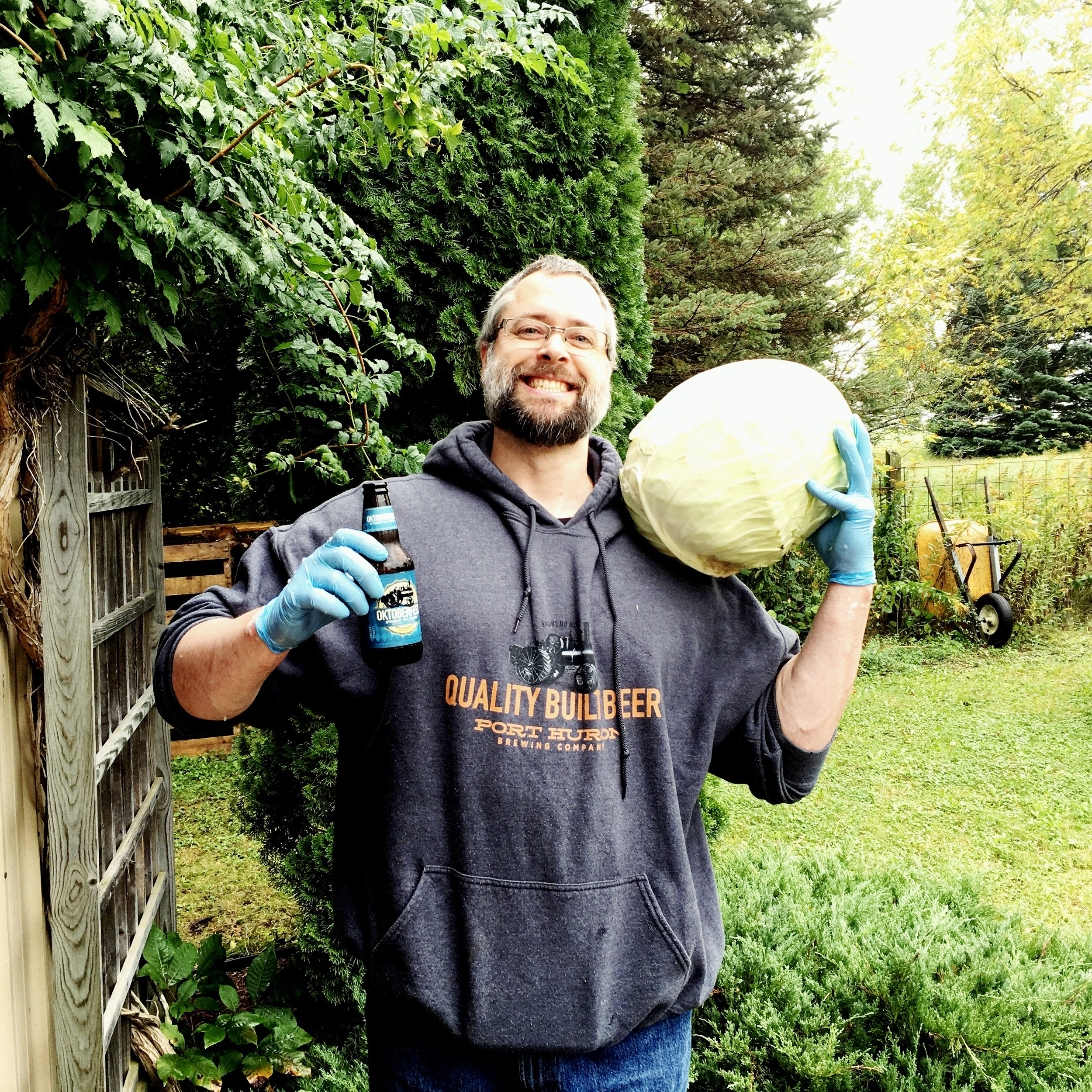 Mr. Yarnista shows off his coordinated  Port Huron Brewery  attire and beer, while holding a 10lb head of cabbage (and this was one of the smaller ones).