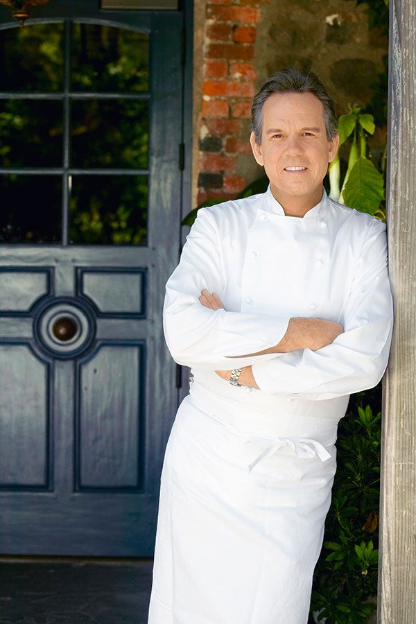 image by  Deborah Jones Studio    Chef Thomas Keller standing in front of the famous blue door of  The French Laundry , that pays homage to the previous owners Don and Sally Schmitt's blue range hood. The color has inspired the restaurant's blue palette ever since.