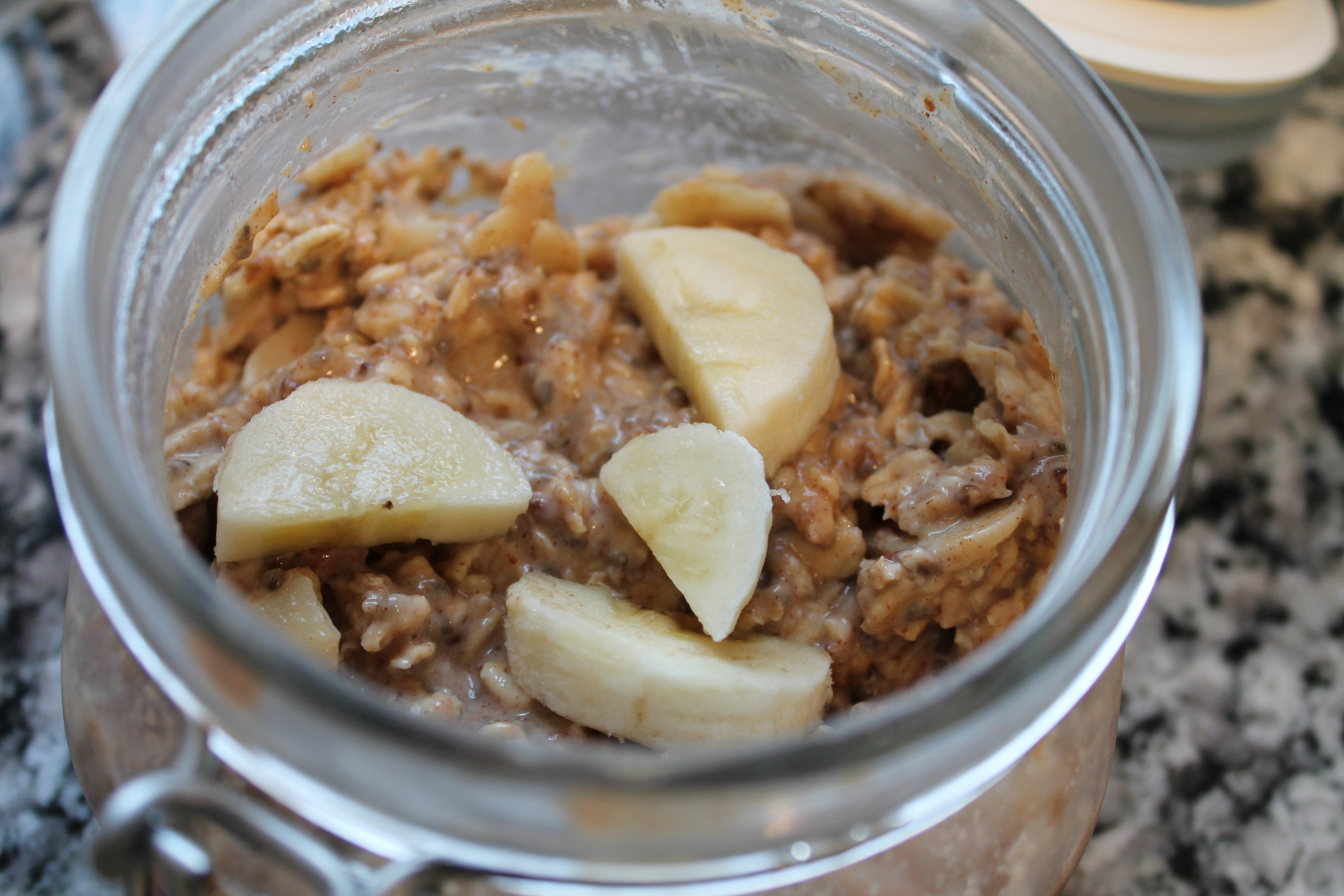 Banana almond butter overnight oats ready to eat, with extra fresh bananas cut on top