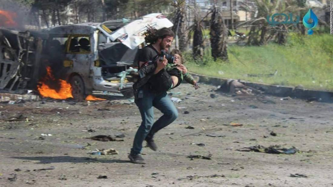 Photographer Abd Alkader Habak rescuing a child in Aleppo after a suicide bomber lured dozens of children with food while they waited for transport buses to safer Syrian areas.