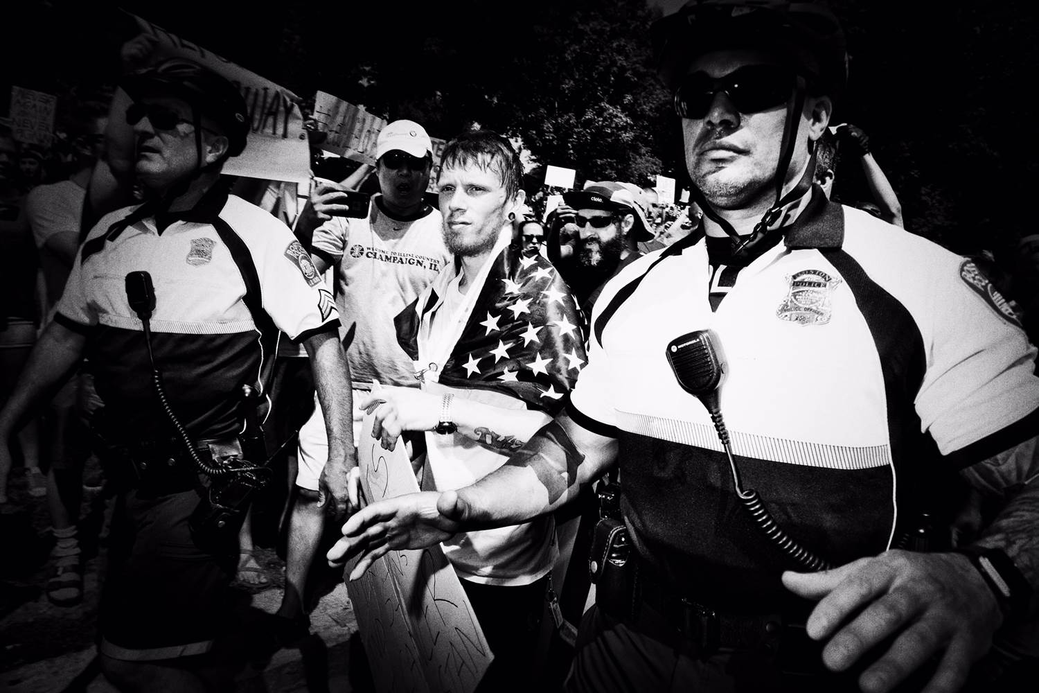 A 'Free Speech Rally' attendee is ushered through the crowd of protesters by police. Mark Peterson / Redux for NBC News