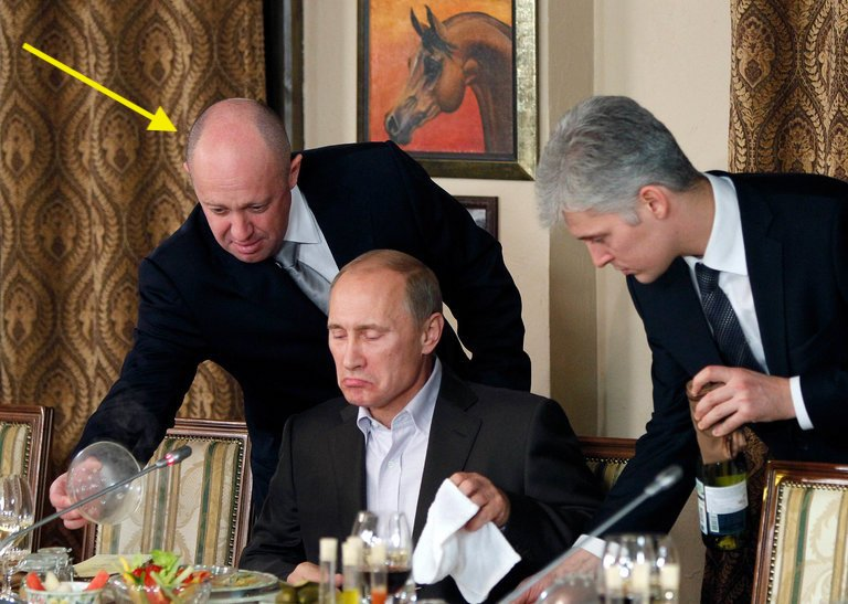 Yevgeny V. Prigozhin, left, serving dinner to Vladimir V. Putin in Moscow in 2011, when Mr. Putin was prime minister.  Mr. Prigozhin has emerged as Mr. Putin's go-to oligarch for sensitive and often-unsavory missions like the troll factory — called the Internet Research Agency — or recruiting contract soldiers to fight in Ukraine and Syria.