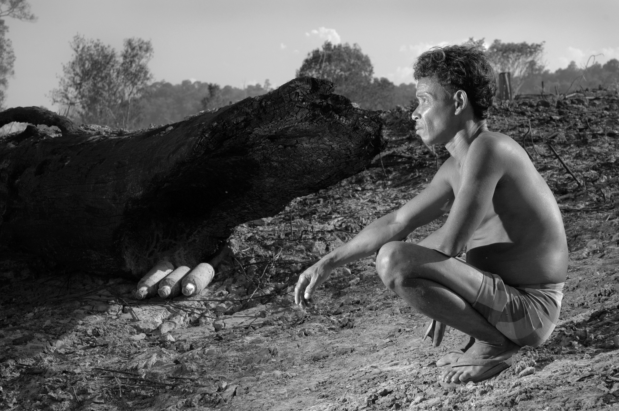 """Tao Lee squats next to three M1 fragmentation cluster bombs found in a cleared field overlooking Etoum, southern Laos. When the field was lit to clear it for farming, the fire """"cooked off"""" several other bombs. They rained shrapnel on the village in the middle of the night, forcing its temporary evacuation."""
