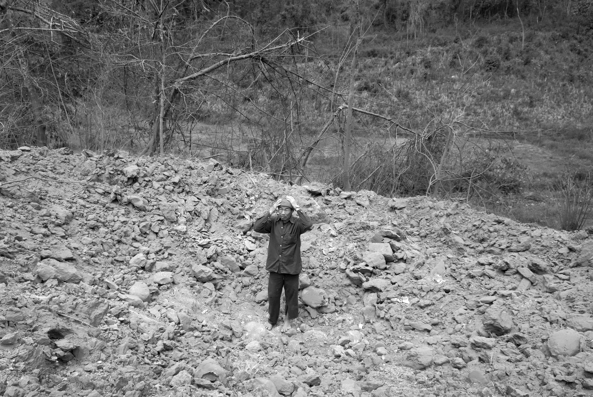 A local man clasps his head in disbelief as he stands in the massive new crater left by a 750-pound American bomb, in rural Phongsali Province, Laos. A bomb disposal group destroyed the bomb which was found by local girl clearing land for a new garden.