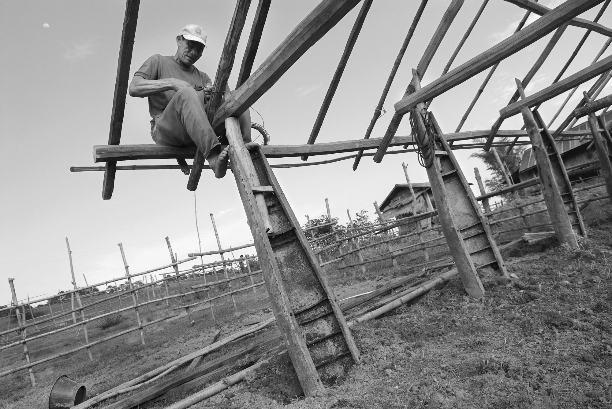 A farmer uses empty cluster bomb casings as pillars for a new animal shelter on his farm in rural Xiengkhouang Province, Laos. The casings, made of well-painted, high-quality steel are valuable for their structural properties as well as their value on the scrap metal market.