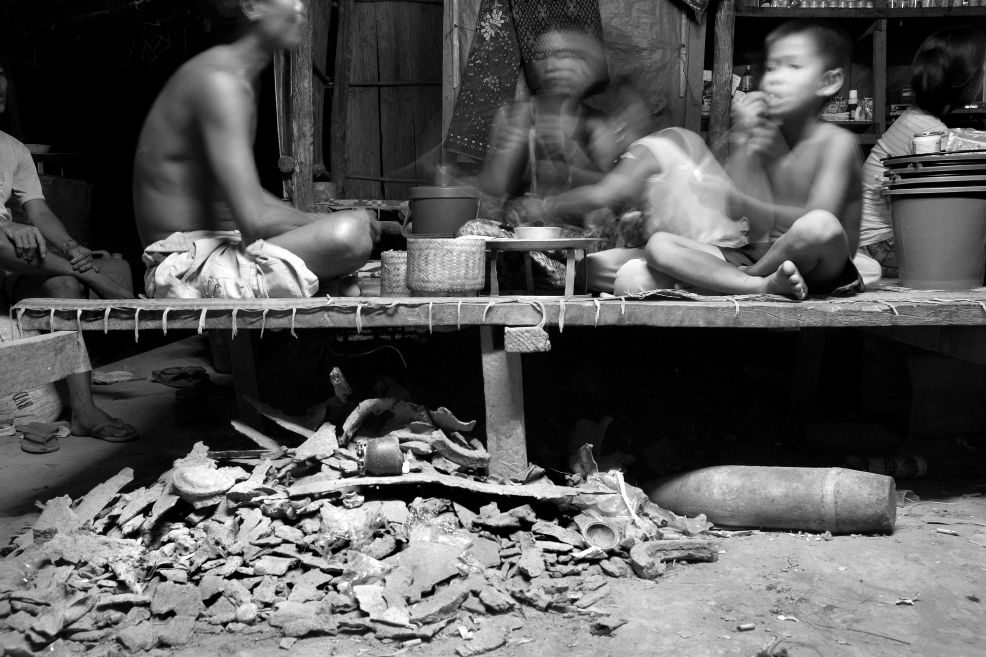 A Vietnamese trader's family has dinner over a pile of bomb shrapnel, cluster bombs and an artillery shell in their hut in Etoum, Attapeu Province, Laos. Vietnamese traders come to the area to buy scrap metal from locals who collect it in the surrounding fields and forest.