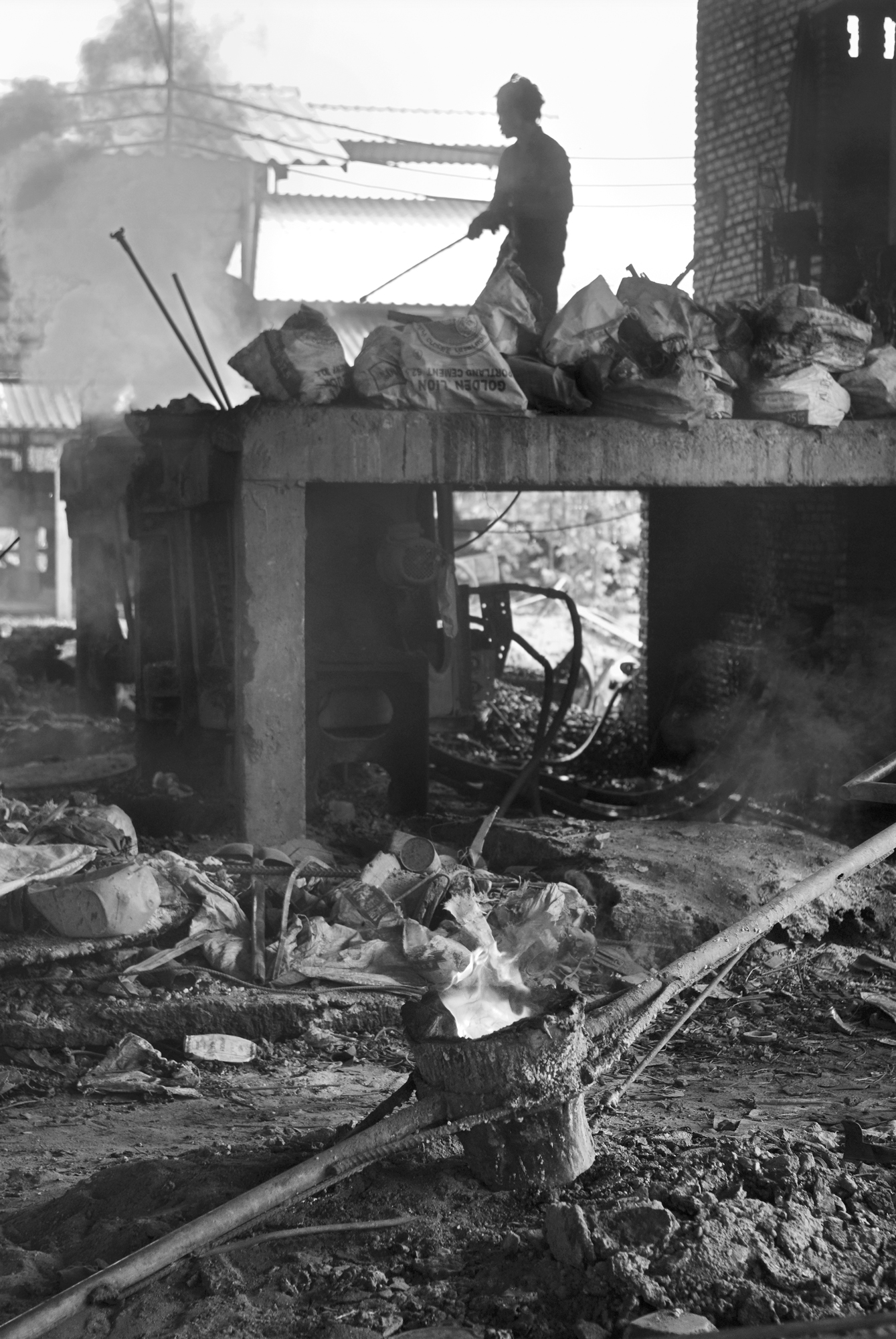 A man smelts scrap metal, much of it war and bomb scrap, in a foundry near Paksan, Laos. Several foundries buy bomb scrap from the Lao countryside which they melt into new rebar for making buildings.