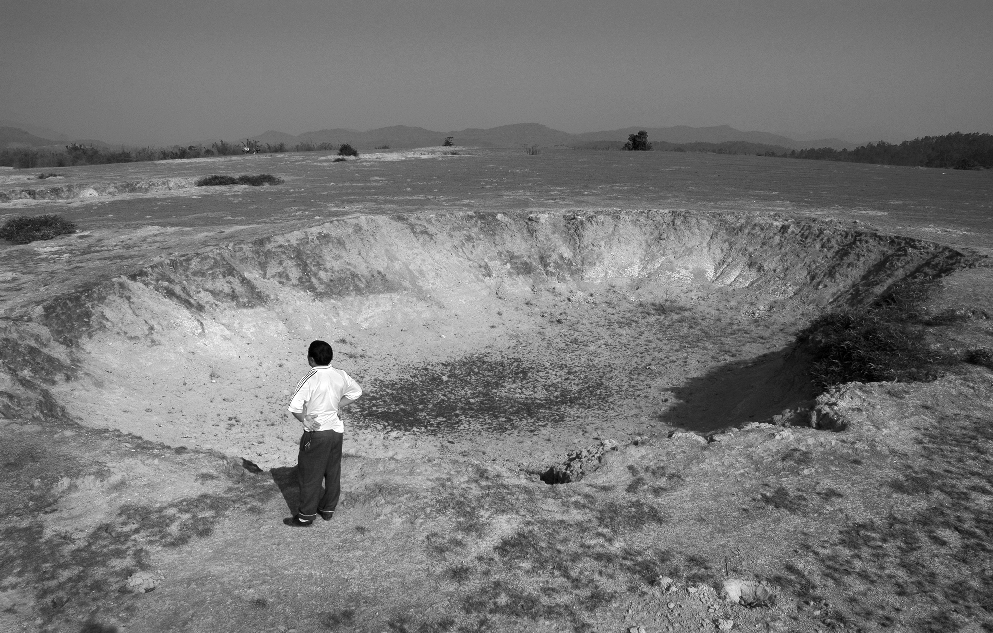 A man stands next to a 40-year-old bomb crater, one of dozens in a line stretching for miles near the Plain of Jars, in Northern Laos. Nothing grows in the craters, and people still pick shrapnel fragments from the surrounding ground.