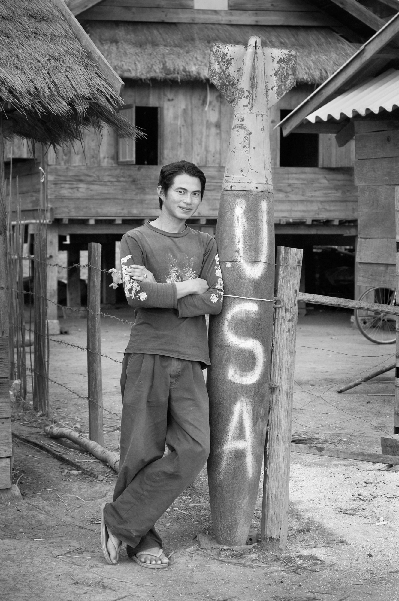 Sou Lin Phan poses next to a large dud bomb in the middle of his village in rural Xiengkhouang Province, Laos. Over several years in the late 60s and early 70s, the US dropped 4 billion pounds of explosives on northern Laos in a futile effort to stop North Vietnamese soldiers from using the area as a base and transshipment line to South Vietnam.