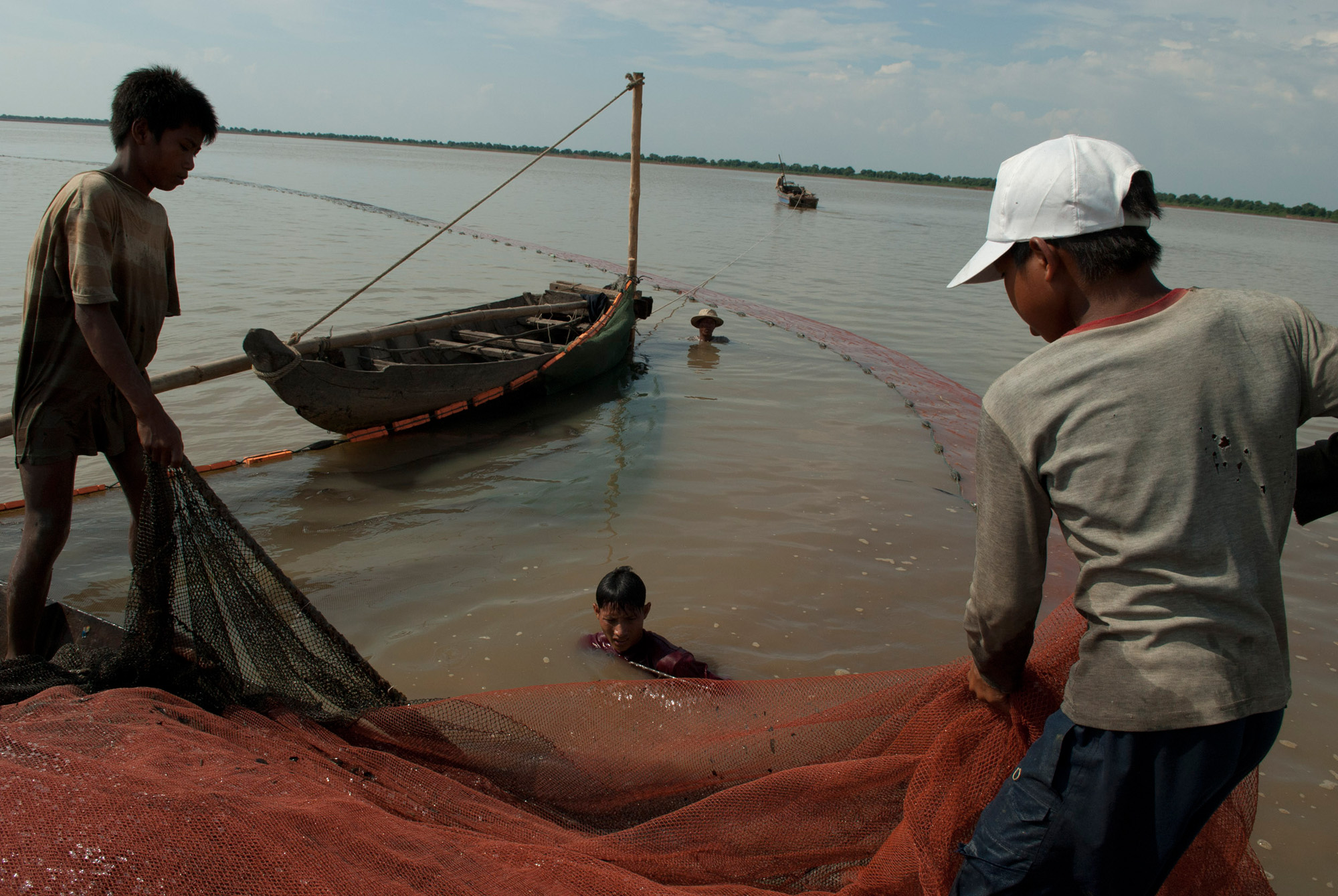 Boys pull in a fishing net on the Tonle Sap lake in Cambodia.