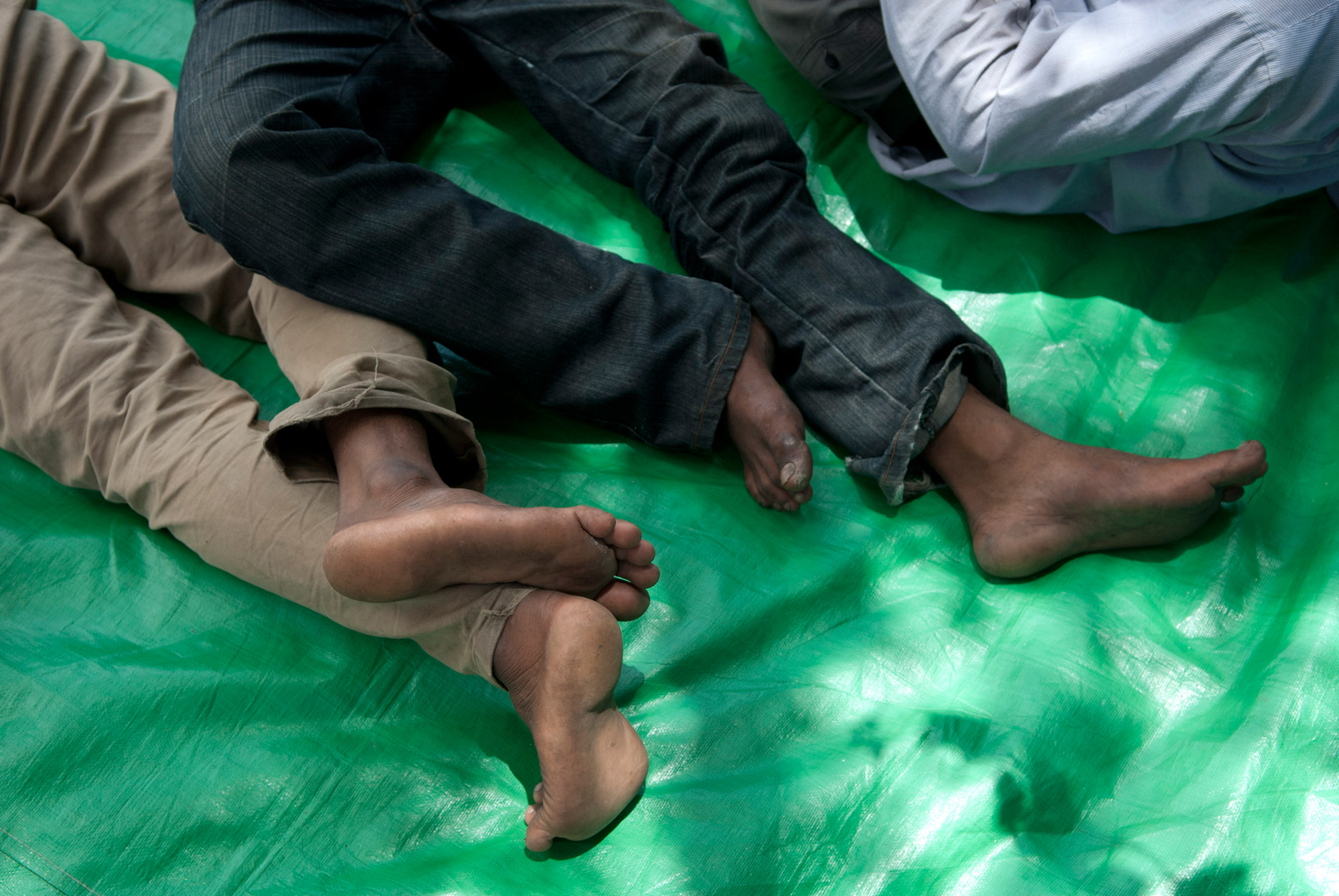 Evicted farmers nap on a tarp during a days-long protest in front of the Cambodian National Assembly Building.