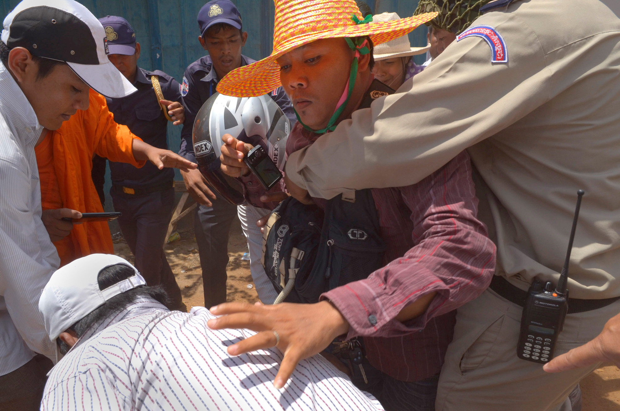 A human rights monitor is manhandled by police as he tries to film an arrest at a protest at the former Boeung Kak Lake in Phnom Penh. Police arrested twelve women for protesting the loss of their homes to a commercial development by Shukaku Corporation, which has since filled in the lake with sand.