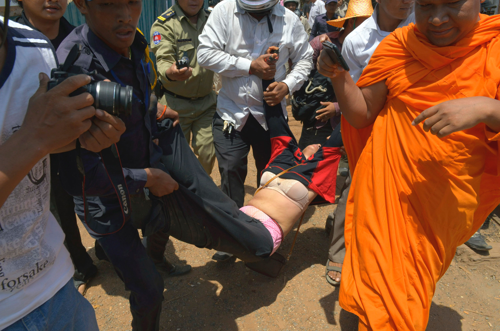 Police carry a protestor to a waiting police van following her arrest. Buddhist monk Loun Saveth videotapes the proceedings. He was arrested two days later. The woman was one of twelve arrested for protesting the loss of their homes at Boeung Kak. The protestors were forced out of their homes along the lakefront by the land developer and the municipal government.