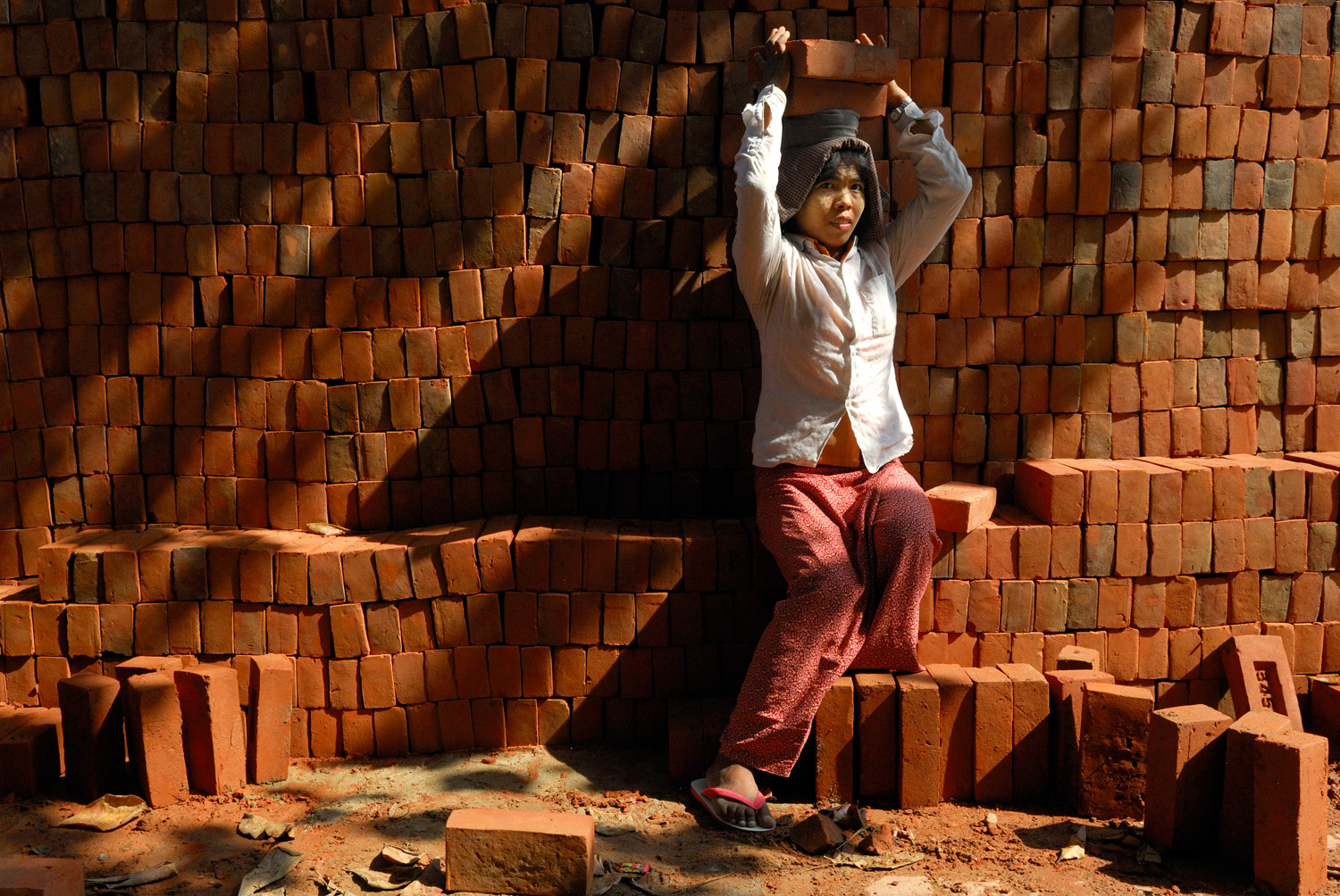 A woman carries bricks atop her head at a construction site in Mandalay, Myanmar.