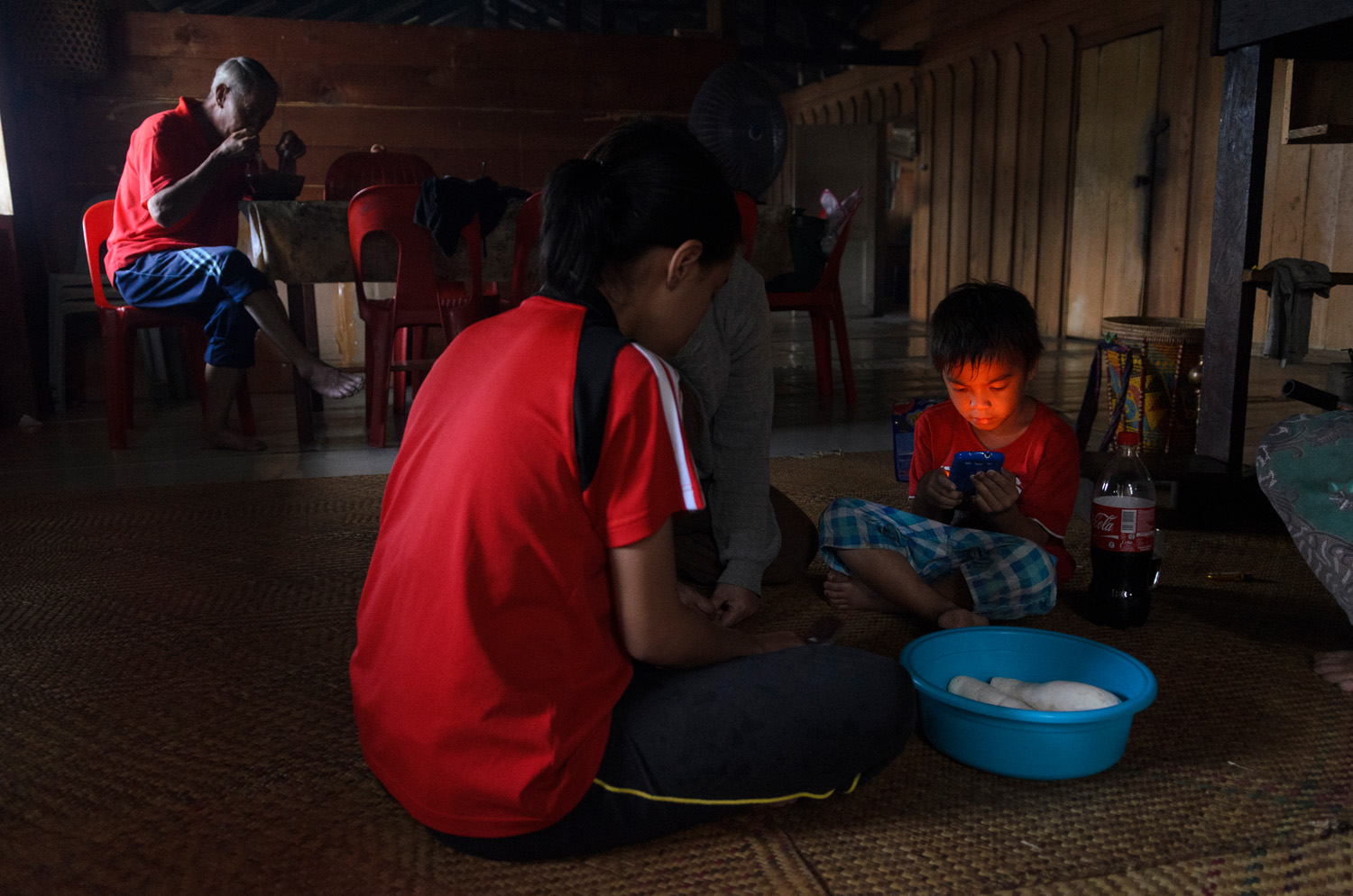 The Parill family tend to different activities in the great room of the Bario Asal longhouse: grandfather eating, mother and daughter cleaning food and young son playing games on a cell phone.