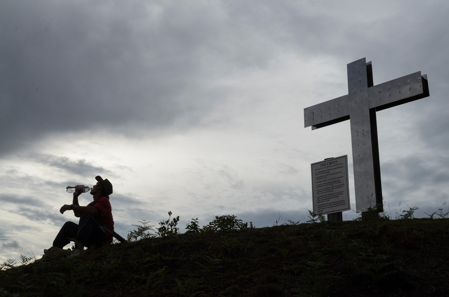 Walter Paran takes a drink of water atop a hill overlooking Pa Lungan village deep in the Kelabit Highlands of Sarawak, Malaysia. The cross is a recent addition, and a reflection of the local christian culture, as opposed to the majority Islam of Malaysia.