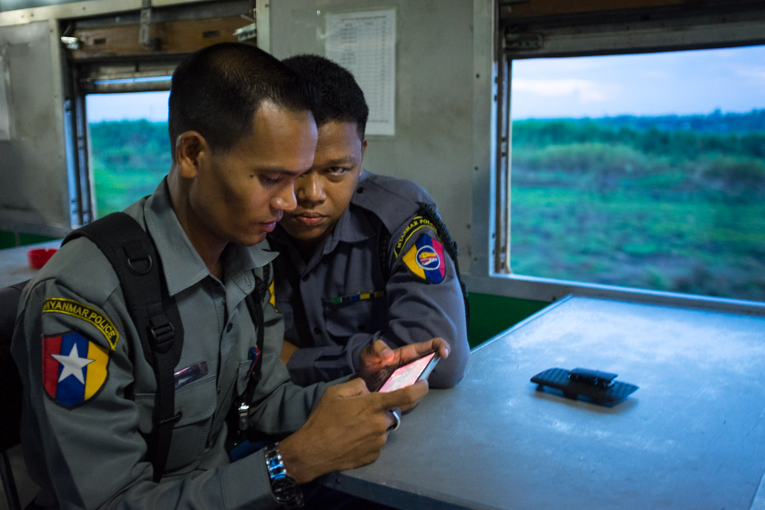 Myanmar Police officers play video games on the Yangon - Mandalay train.