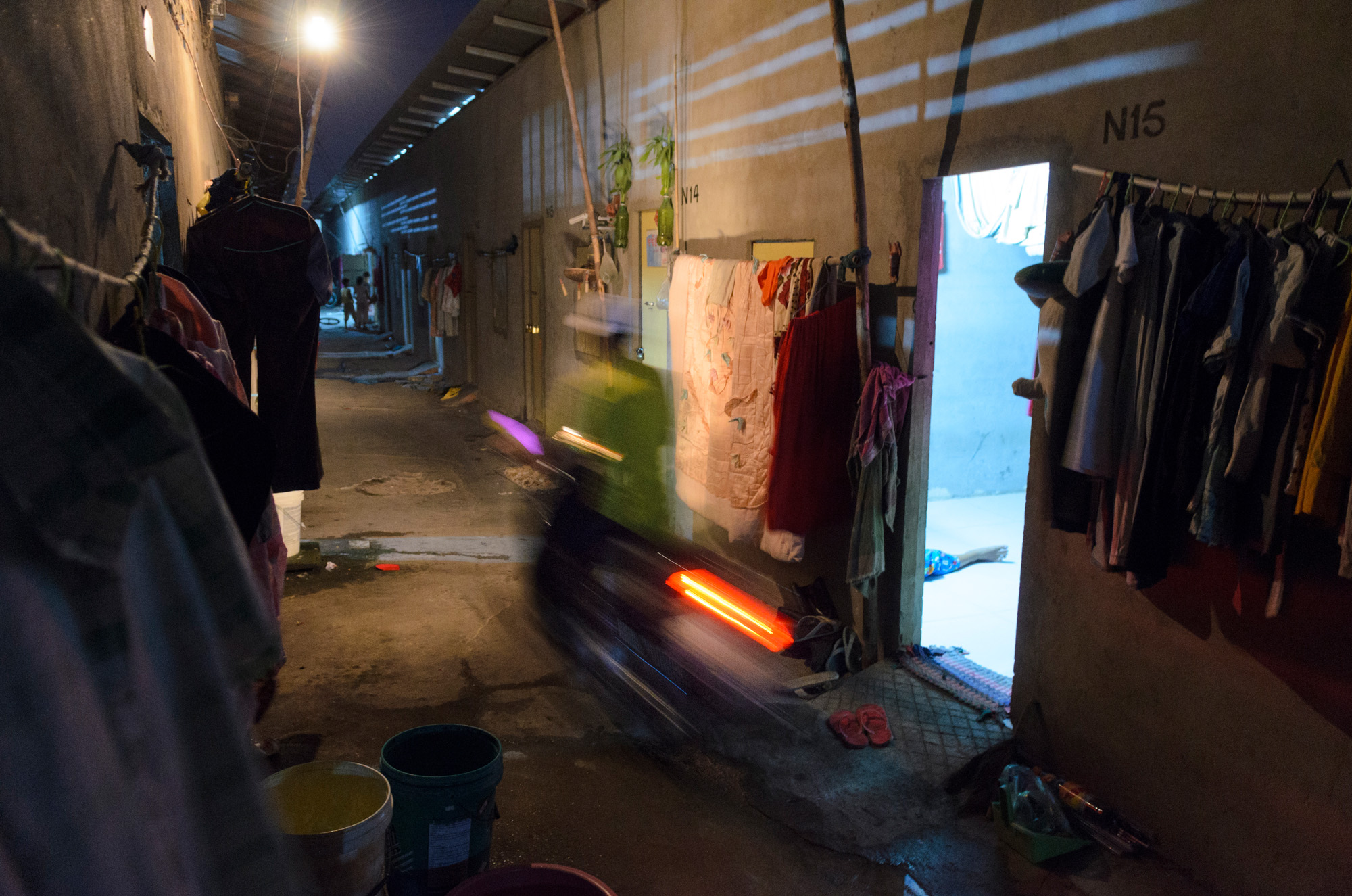 A man drives a motorcycle through the narrow alleyways connecting apartments in a low-rent housing development that caters to garment factory workers on the edge of Phnom Penh, Cambodia.