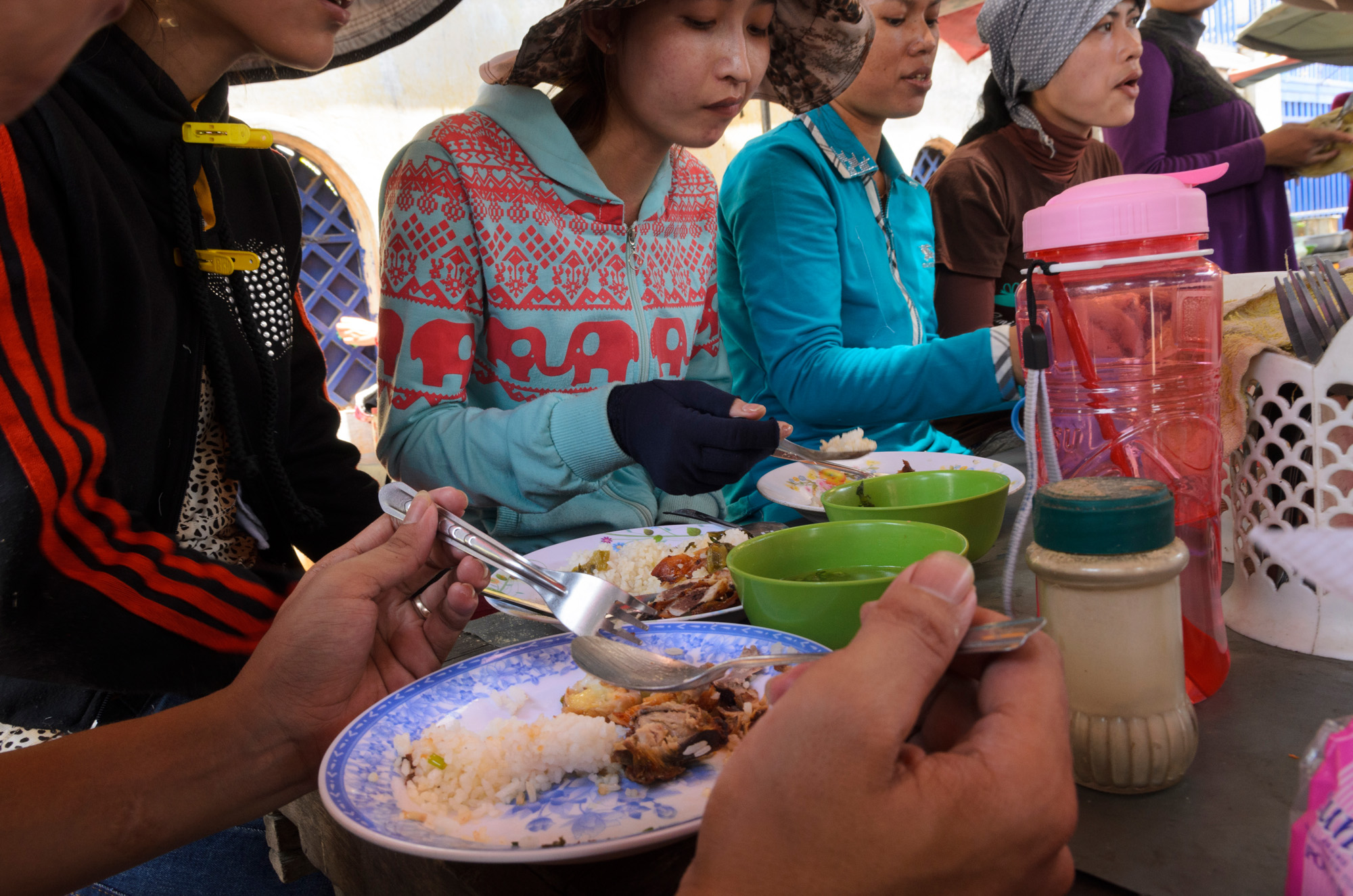 Young women eat  lunches of rice and soup at a food stall outside a factory on the northern outskirts of Phnom Penh, Cambodia. Recent reports highlight the rate of malnutrition among Cambodia's tens of thousands of garment factory workers.