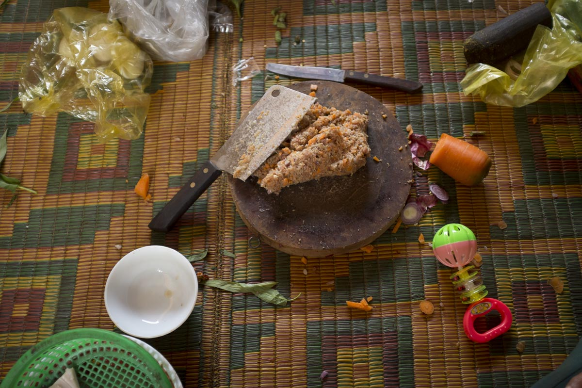 Herm Rithya, also known as Pov, minces chilies and prahok, the traditional Khmer fish paste, at his guesthouse in Banlung, Cambodia.