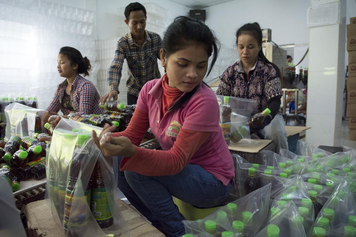 Ya, center, and other workers package bottles at the Leang Leng Fish Sauce Factory in Phnom Penh.