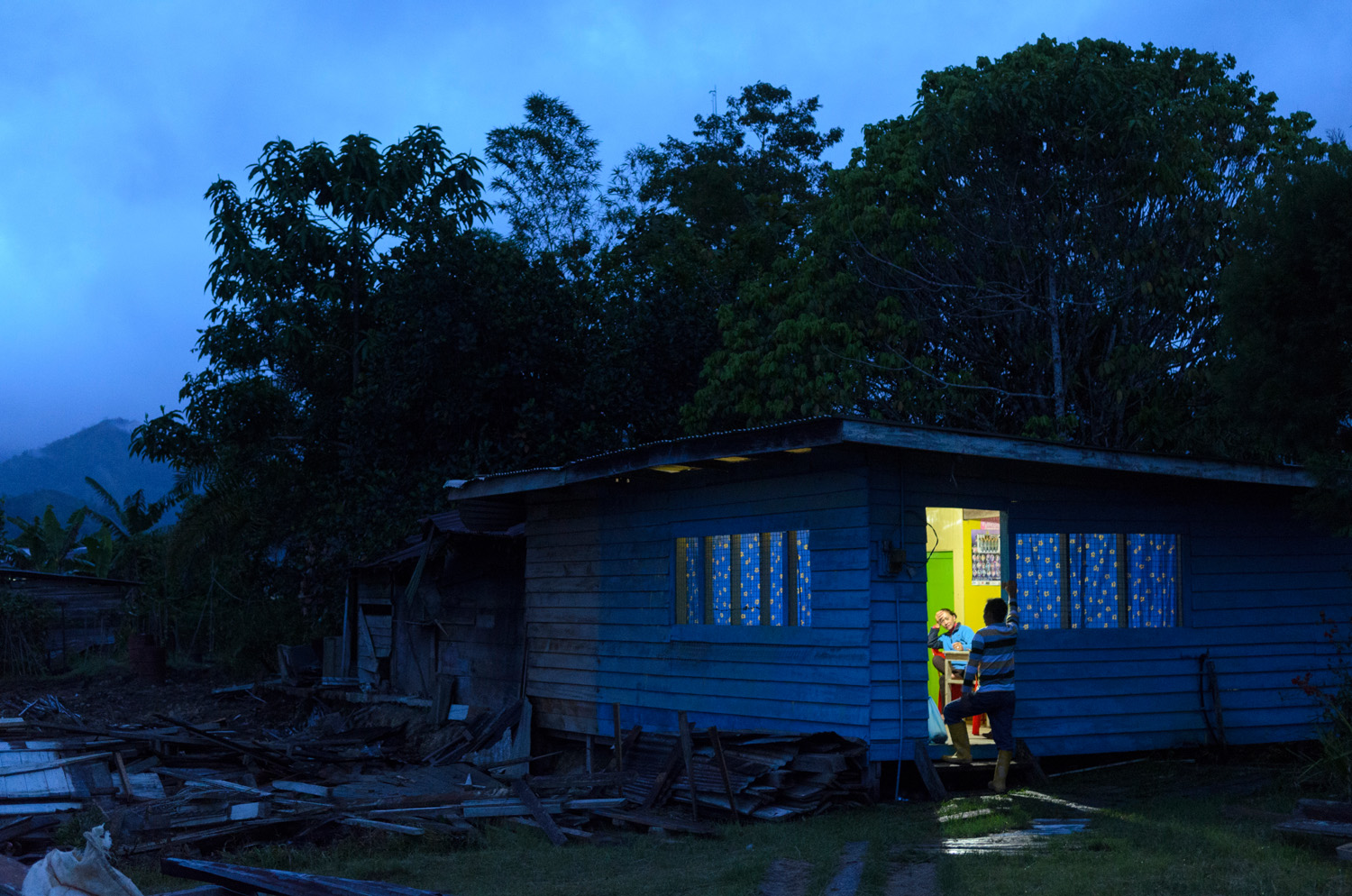 Night falls on a couple having a conversation in the doorway of a house in Bario, Sarawak, Malaysia.