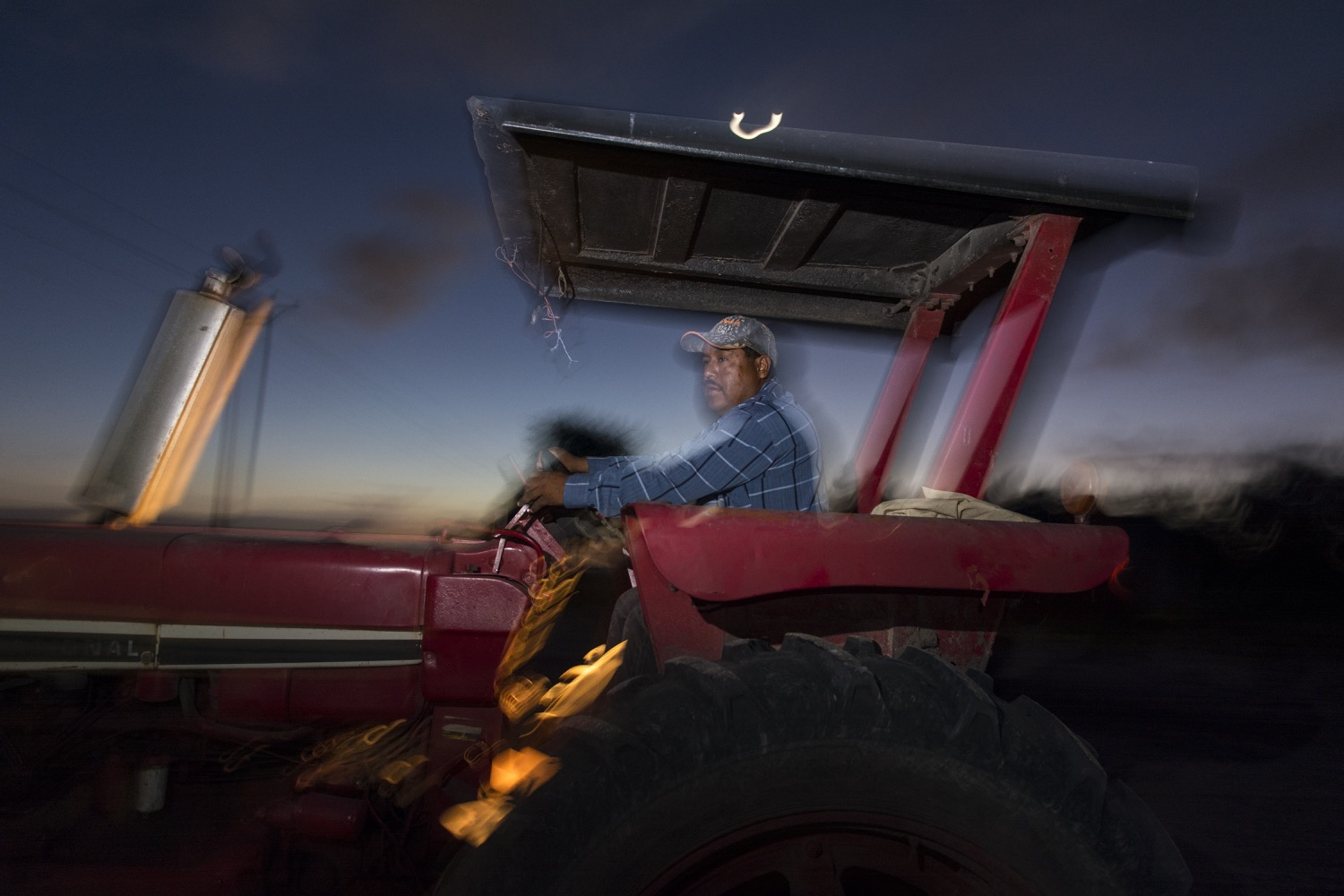 Before dawn, a farmworker starts the tractor he will drive all day in the sugarcane fields of South Texas. ©2018/Jerry Redfern