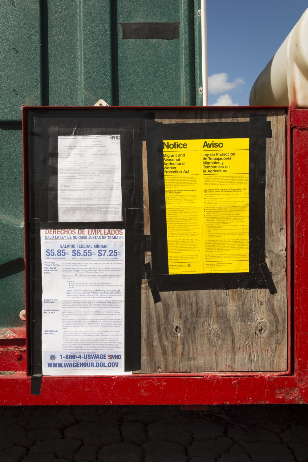 Legal notices of farmworker wages and other laws, taped to the honey wagon at a field outside McAllen, Texas.©2018/Jerry Redfern