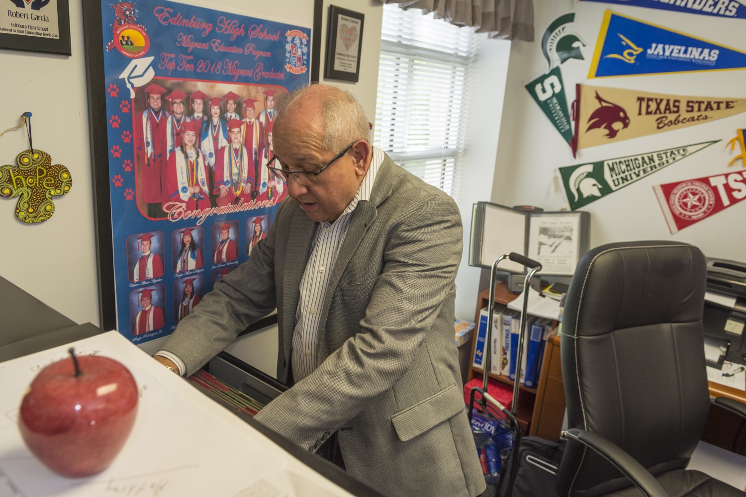 Roberto V. García, migrant student counselor, looks up records in his office in Edinburg High School.©2018/Jerry Redfern