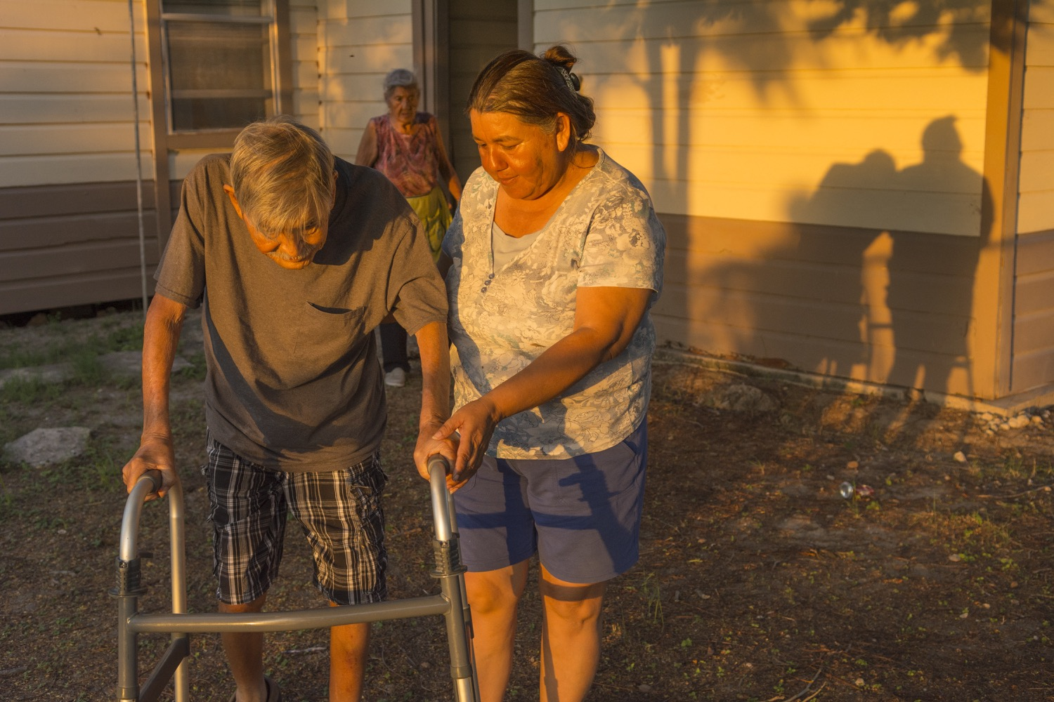 Maria Martinez helps her father, Hermenegildo, walk around their home as Juliana Martinez follows behind. After Hermenegildo suffered a stroke leaving him unable to work or care for himself, Maria took over his job as a field supervisor and helps him around the house they all share.©2018/Jerry Redfern
