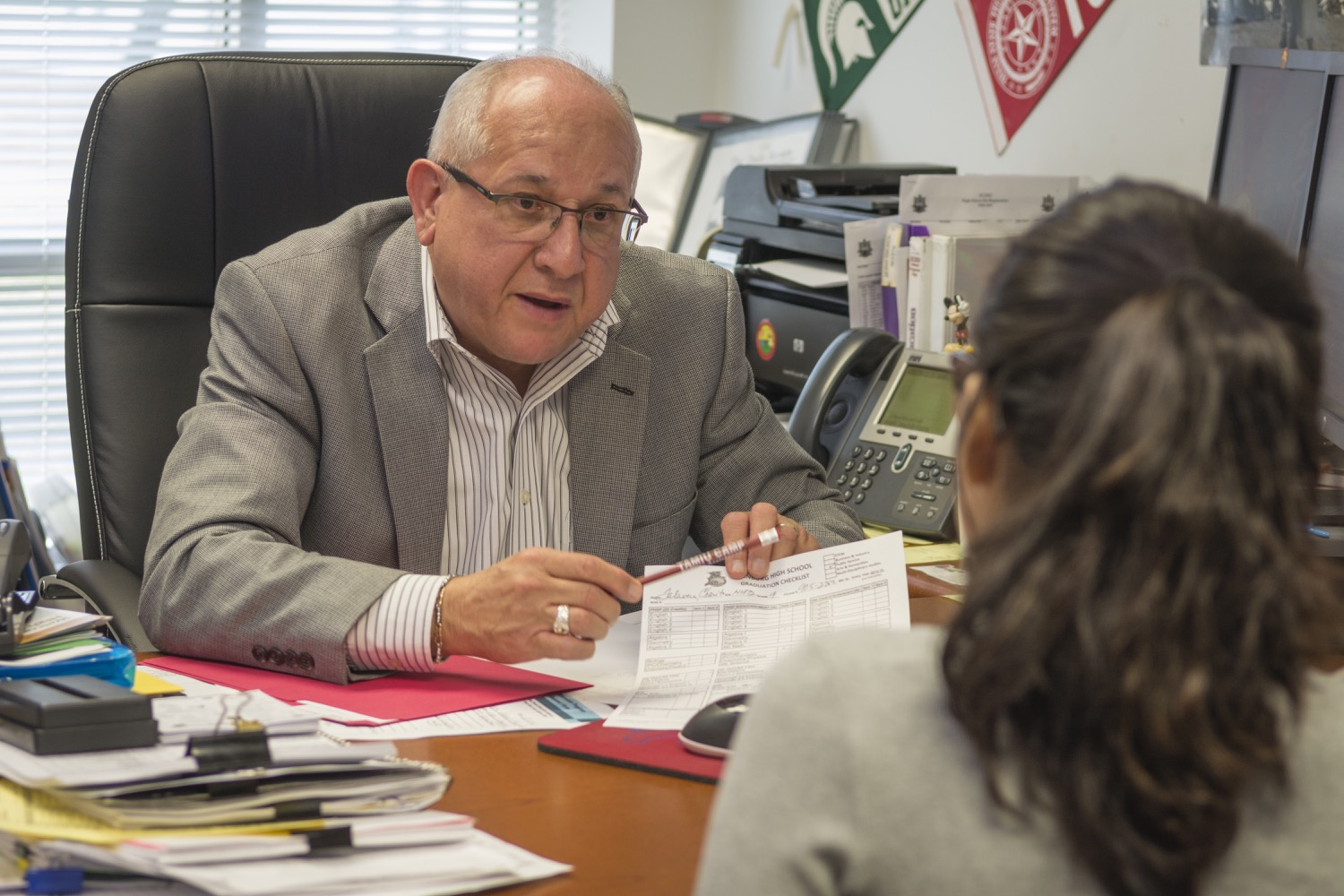 A student talks with Roberto V. García, migrant student counselor, in his office at Edinburg High School. They discus her education and her time spent away from school as her family travels for farm work. ©2018/Jerry Redfern