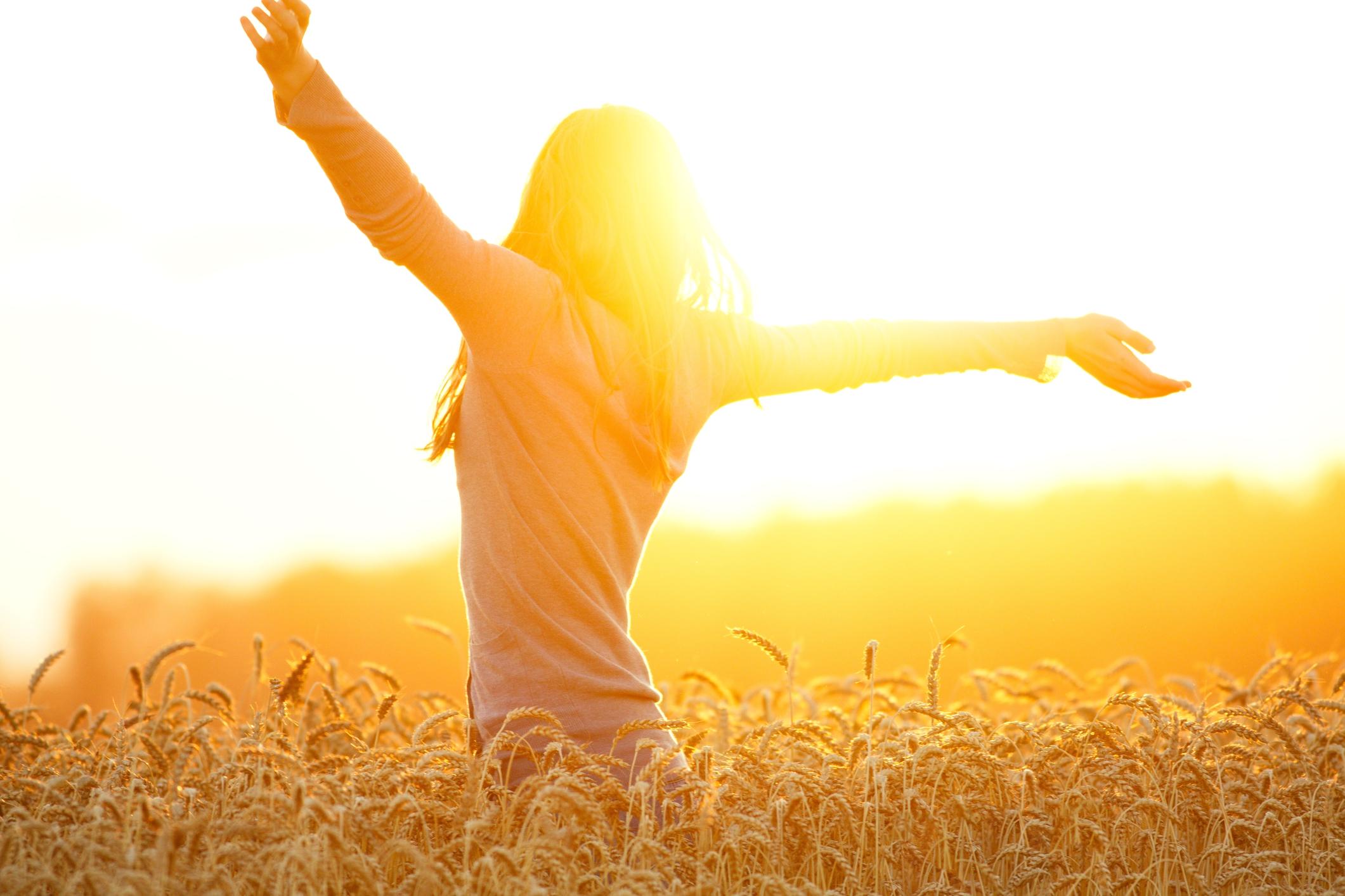 woman arms up sun field.jpg