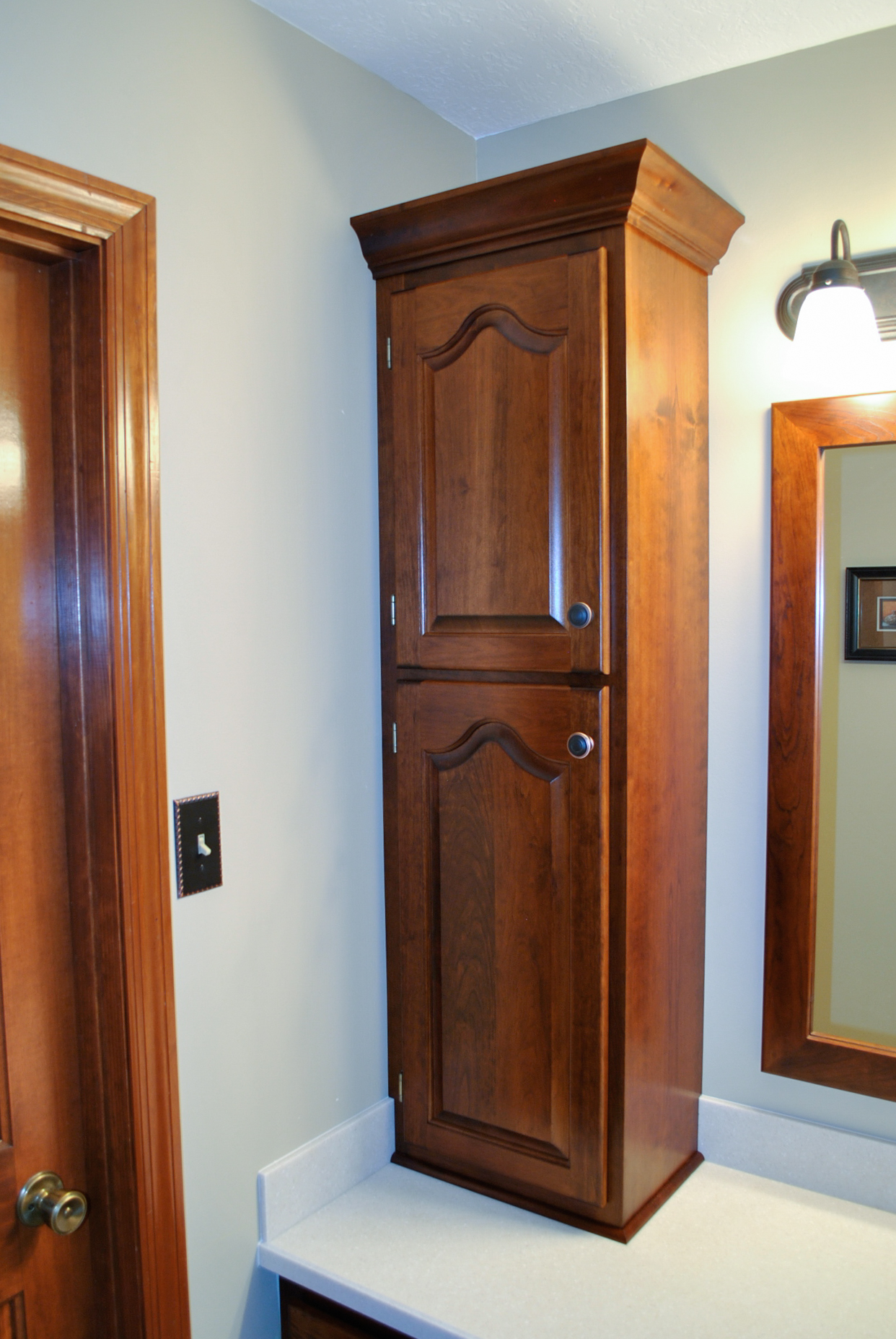 Solid cherry raised panel doors and cabinet custom made to match the existing style.