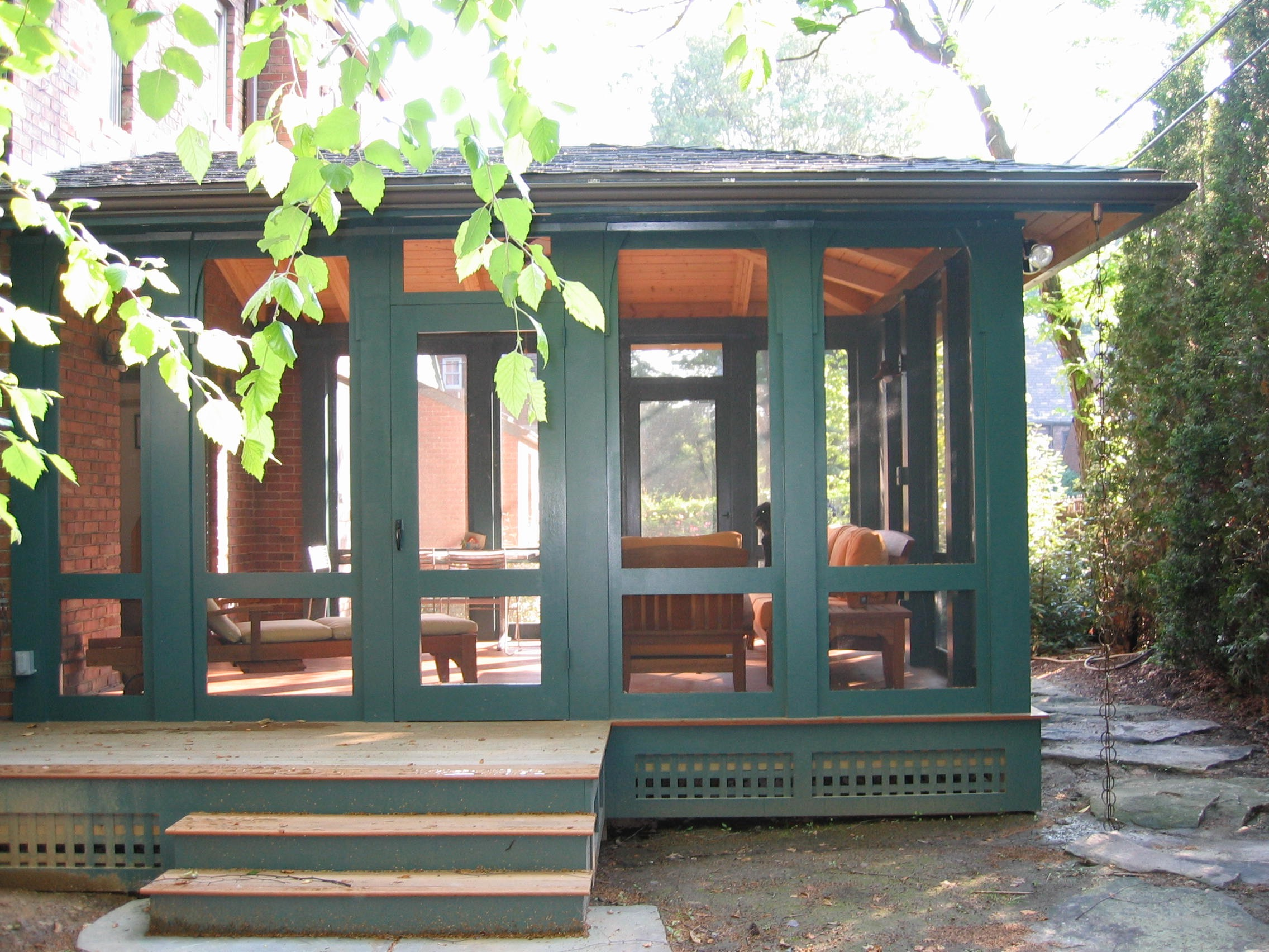 Hip roof porch with screen panels. Bracket detail matches design on main house.