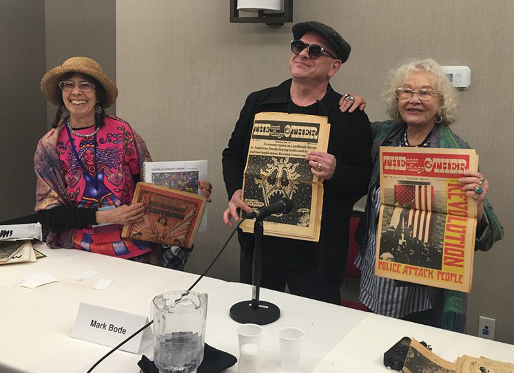 "Barbara ""Willy"" Mendes, Mark Bode, and Trina Robbins hold up copies of the ""East Village Other"" during the ""Gothic Blimp Works"" panel."