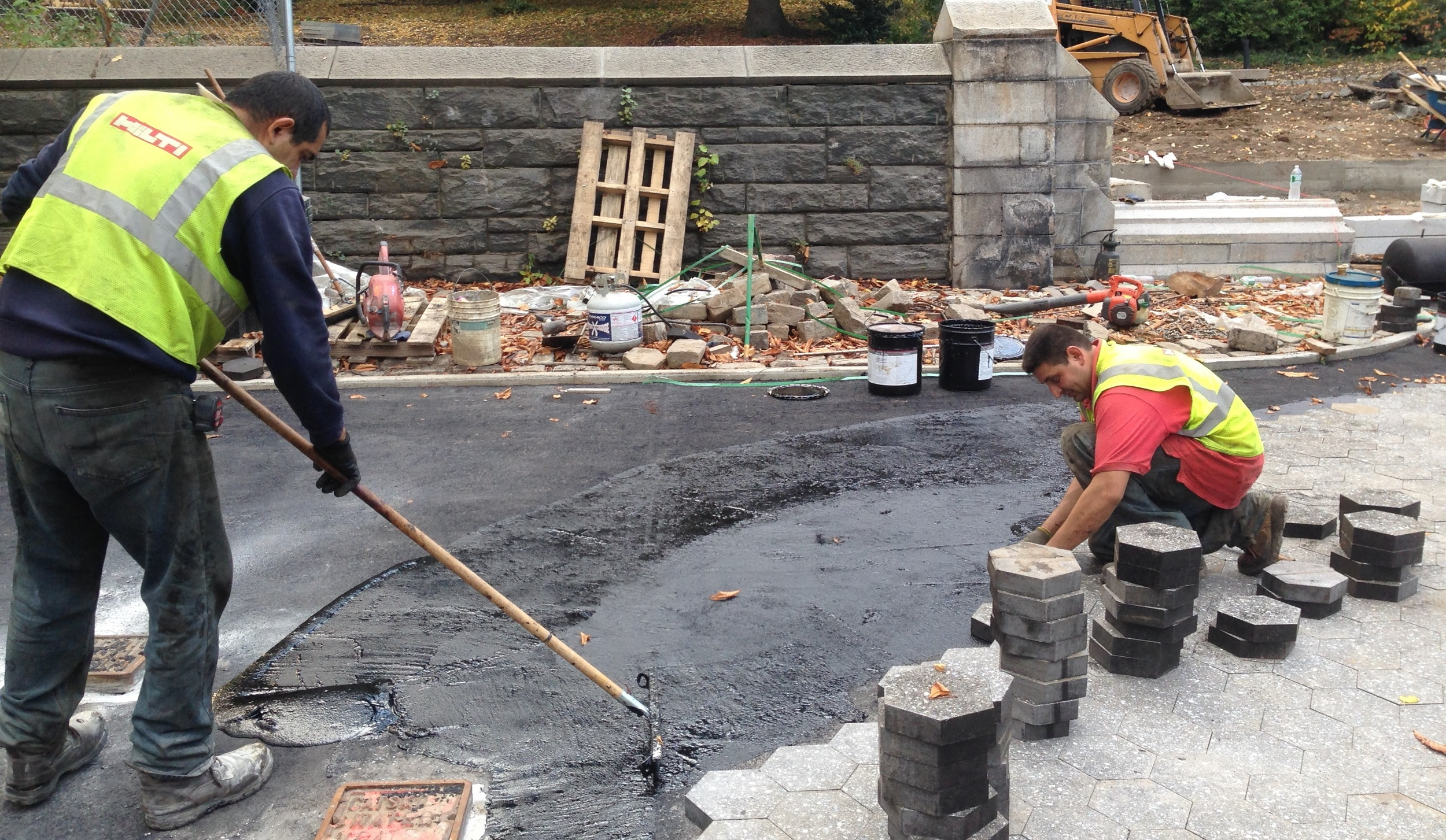 Construction workers laying down hexagonal pavers at the Willoughby entrance way.