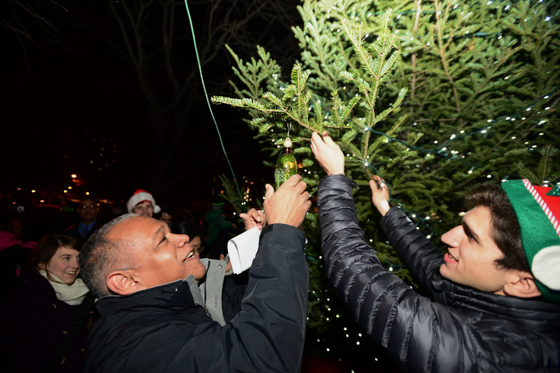 NYC Parks Commissioner Mitchell J. Silver hanging an ornament with FGPC Programming an Development Coordinator Julian Macrone