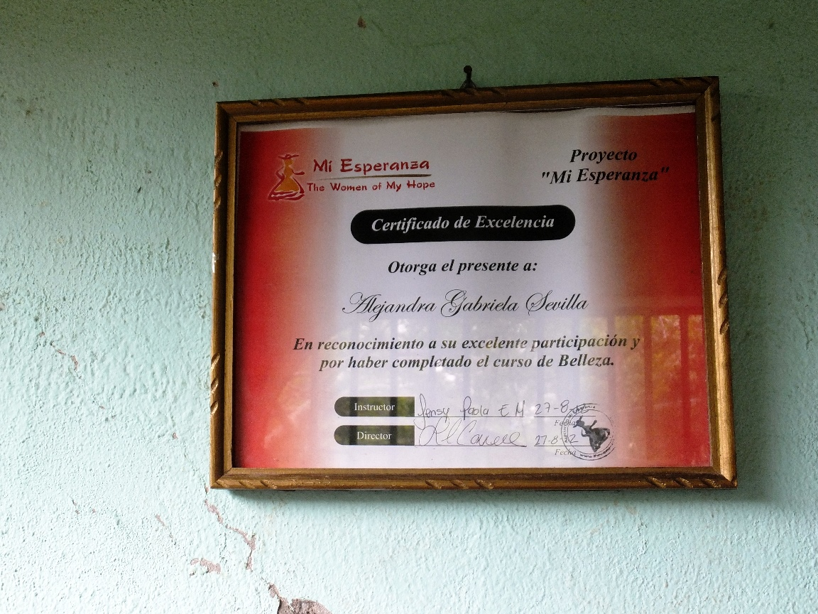 her graduation diploma proudly displayed in her salon