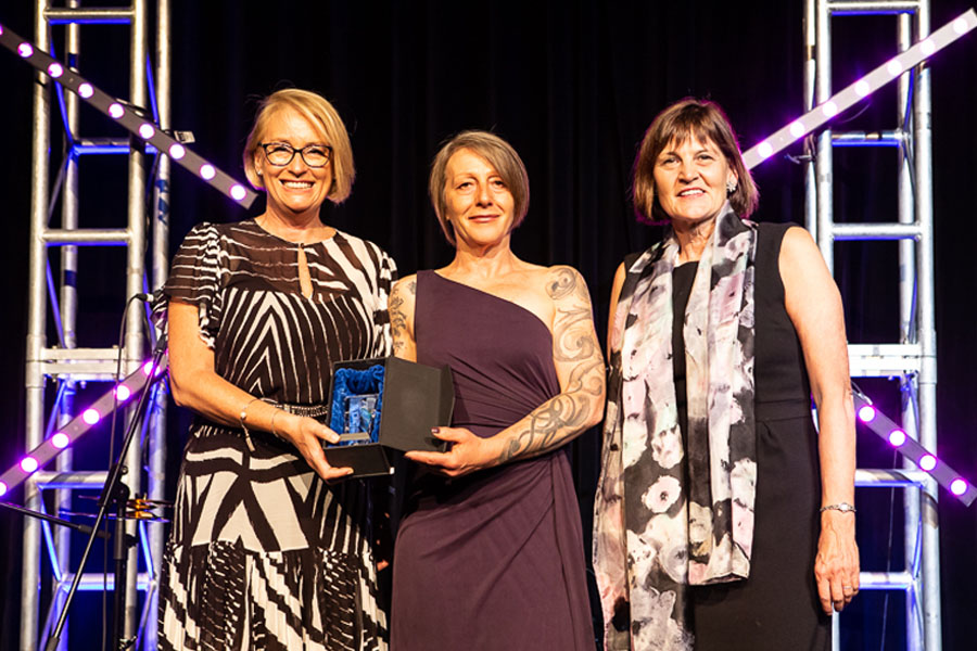 "Zo Damage presented with QVM ""Services To The Community Award"" by Lord Mayor of Melbourne Sally Capp (left), and, QVM Chairperson of the Board Jane Fenton (right). — Photographer: Kristyna Hessova"