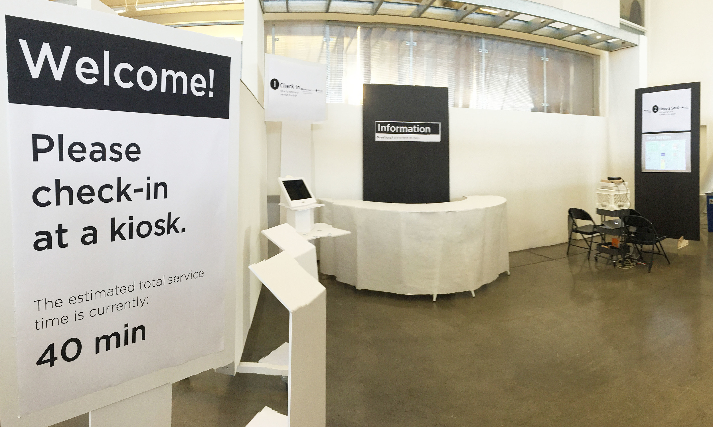 FULL SCALE MODEL:  This photo illustrates our full scale model of our final design. It includes a bank of digital kiosks designed to expedite the application processes, an information booth with a representative available to answer questions and help with forms. a waiting lounge, and text message alerts for clients who prefer to leave the building while they wait for their appointment.