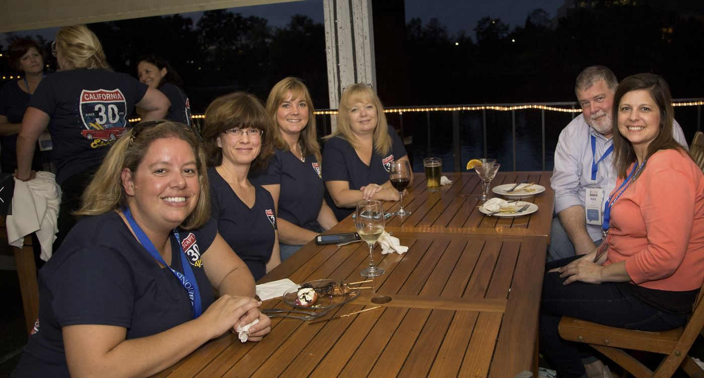 """Attendees showing off their Escape Technology 30-year shirts at the evening """"Beyond Appetizers"""" party at Rio City Cafe."""