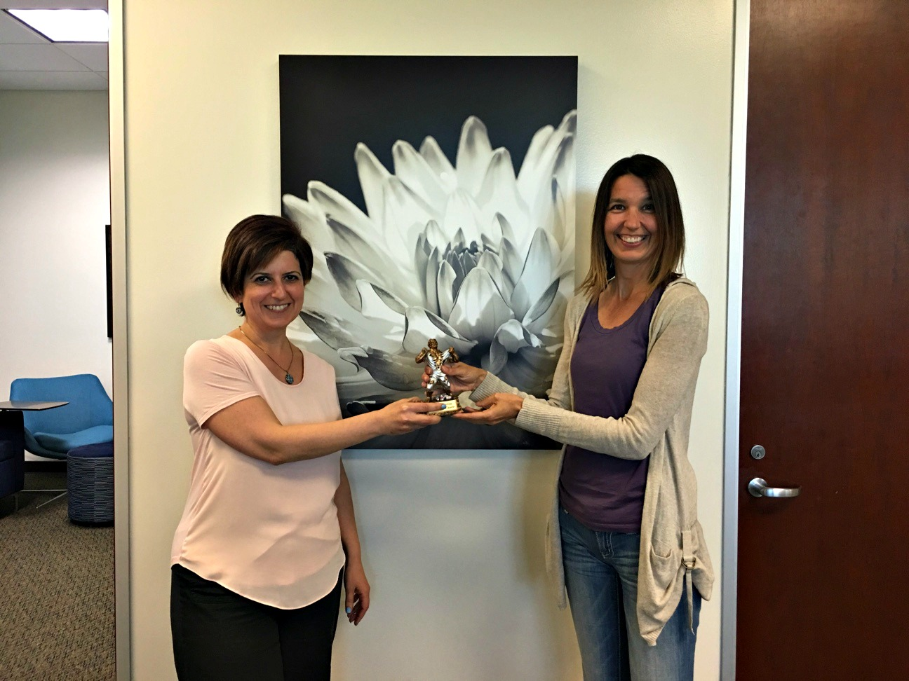 Arin Simonyan, HR/Payroll Software Support Lead and recipient of the Escape Employee of the Second Quarter award, passing the baton to Robin Fiske, Technical Support Analyst and recipient of the Escape Employee of the Third Quarter award.