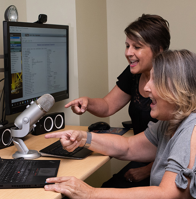Leslie Bailey, Technical Writer, and Terri Hammond, Training Manager, working together in the Escape studio.