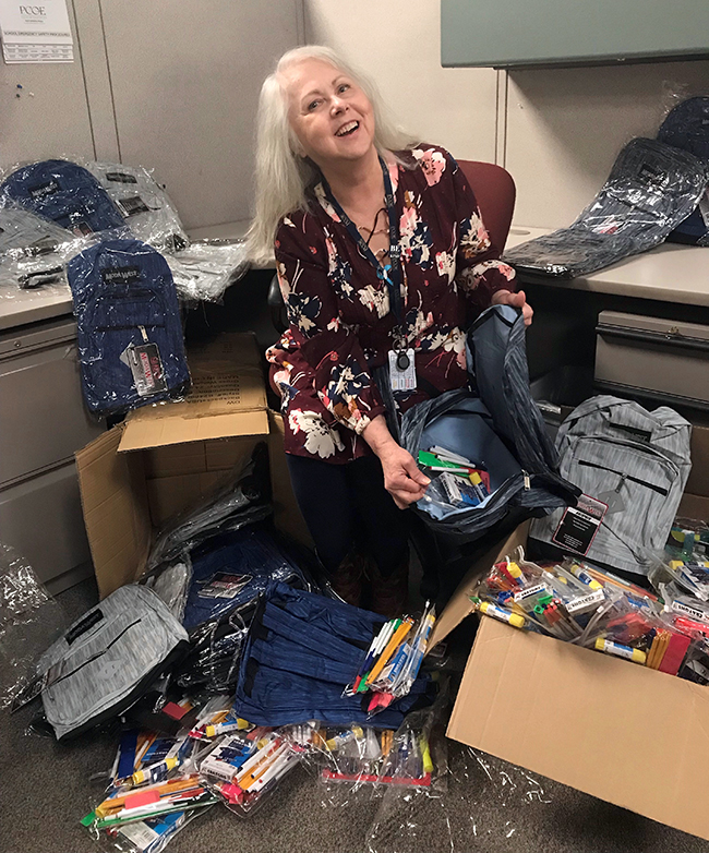 Laura Ralph, Staff Secretary at Placer COE sorts through the donated backpacks and supplies.