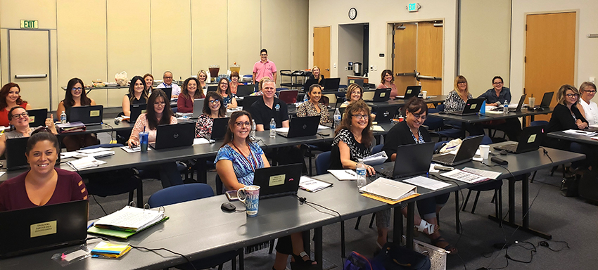 Madera CSOS staff learning about Escape Online in a recent training session. Margie Wells, Escape Implementation Analyst (standing,in pink shirt), watches.