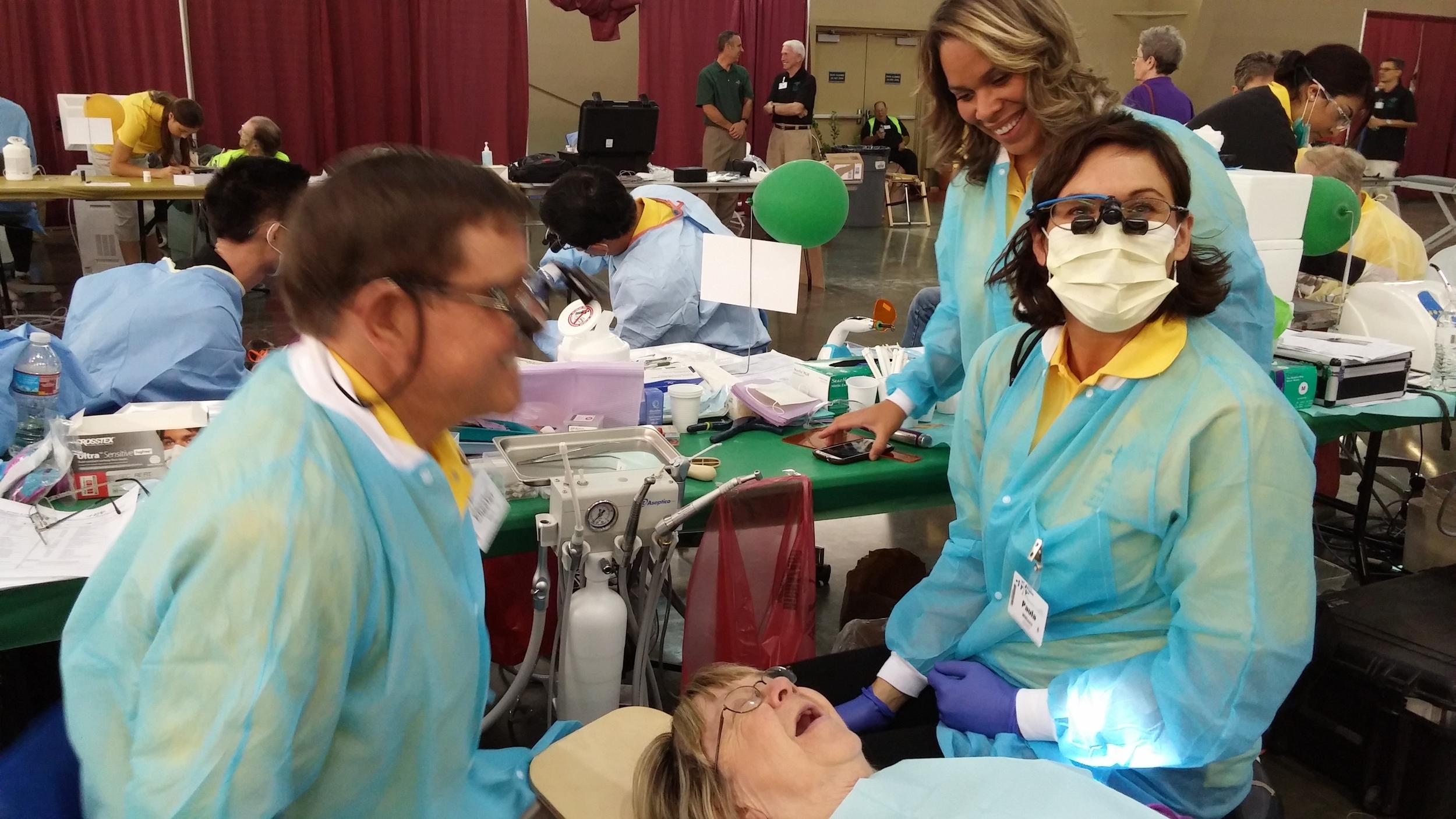 Volunteer dentist and dental assistant provide careatPathwayto Health 2015.