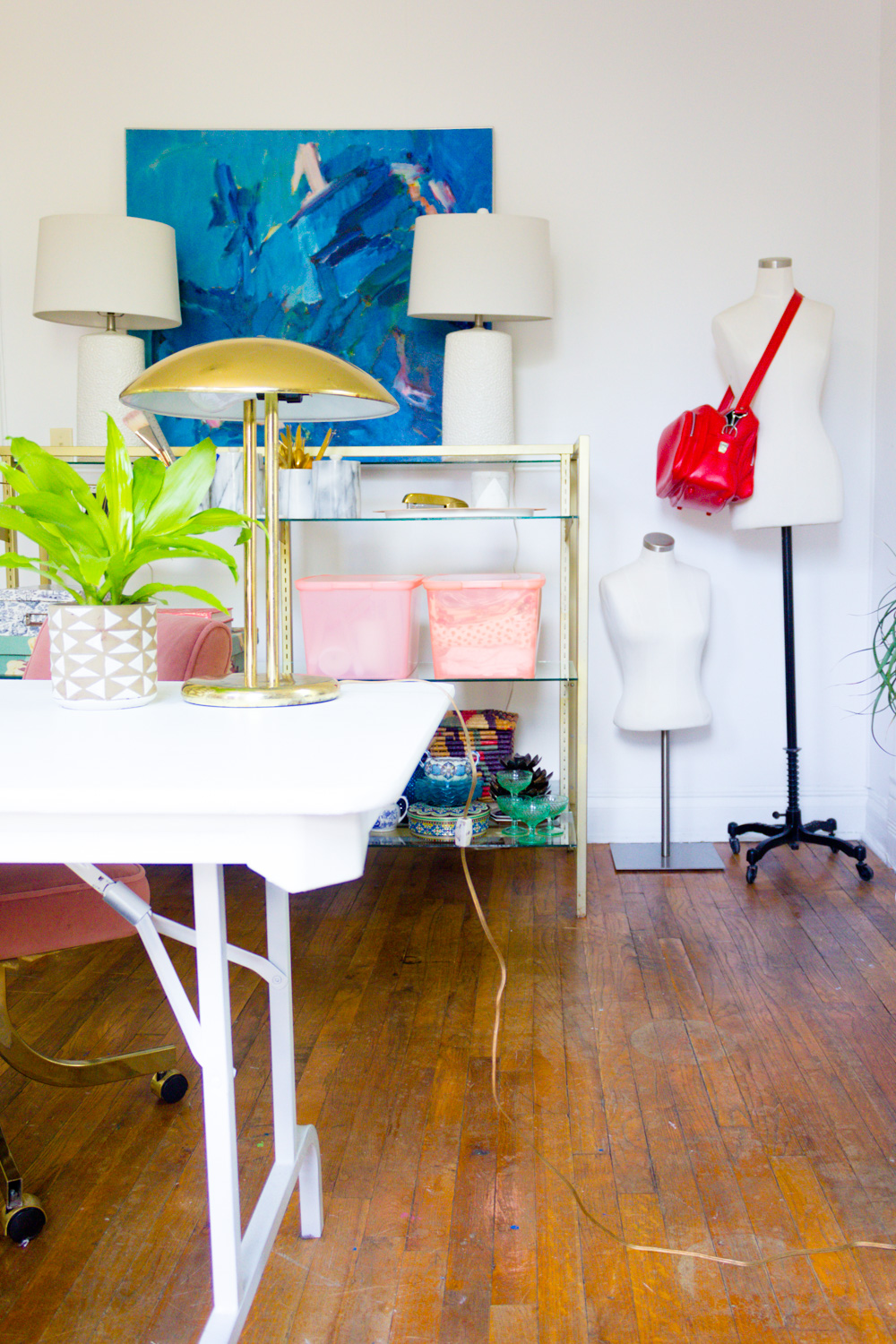 Colorful Home Office with Pink Chairs and Brass Shelving