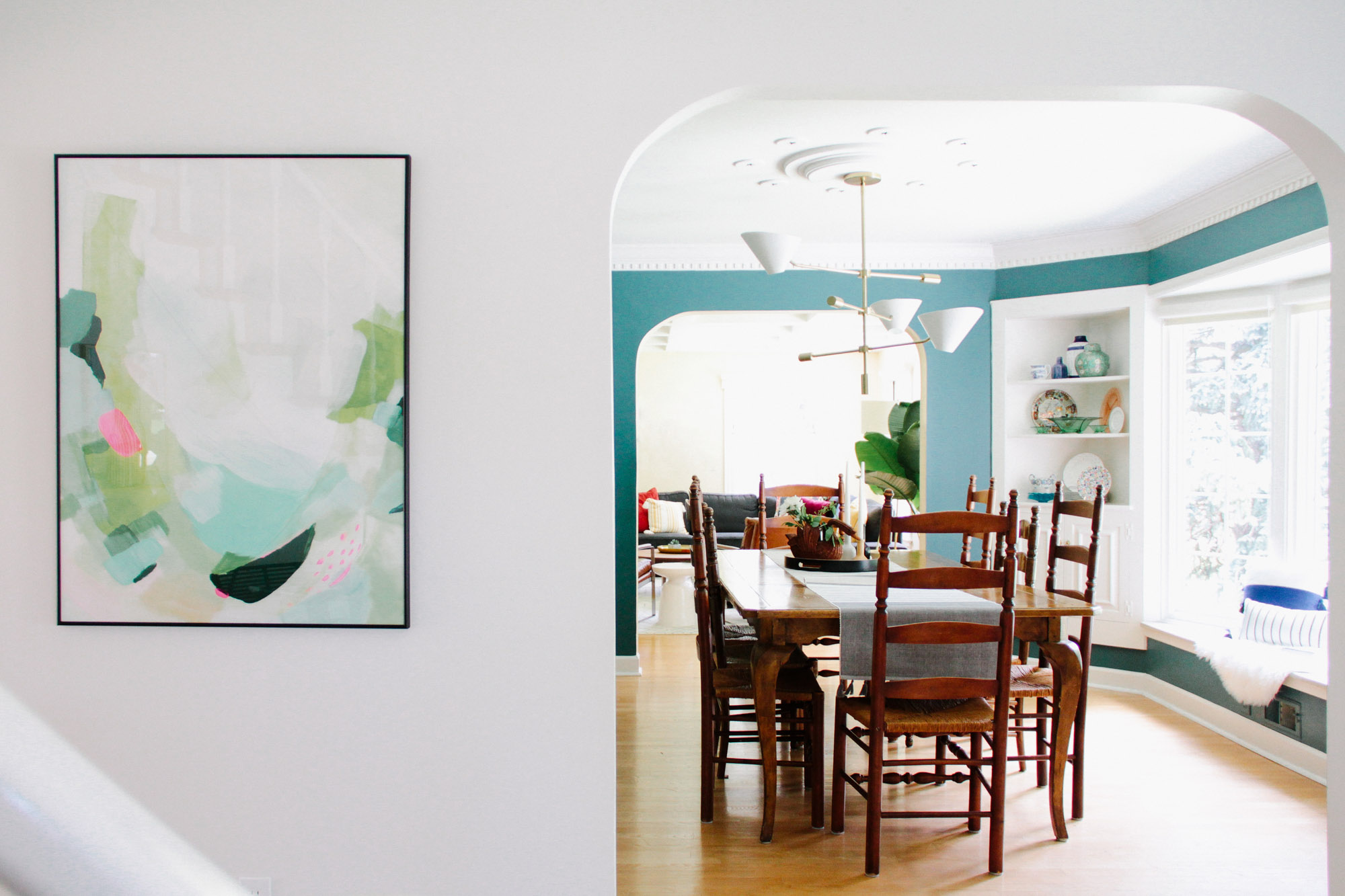 Oversized Abstract Art and Green Walls in Modern Colonial Dining Room