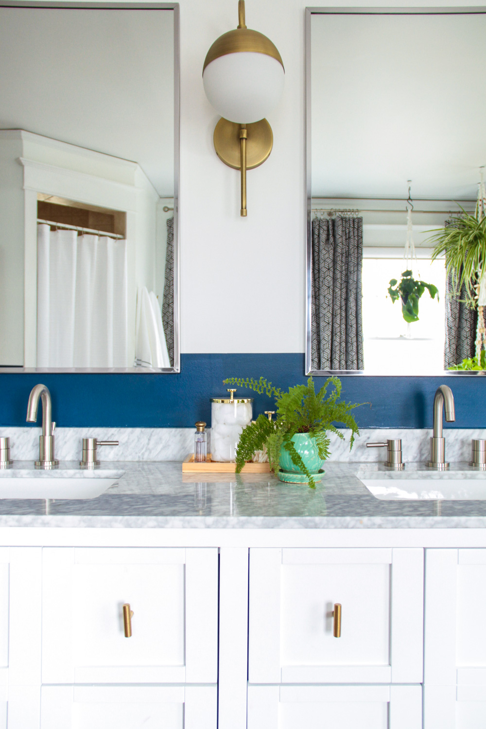 Blue and White Master Bathroom with Plants and Brass Sconces