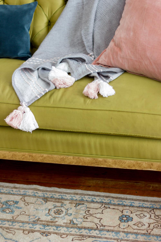 Velvet pillows and tasseled throw blanket on vintage green tufted sofa